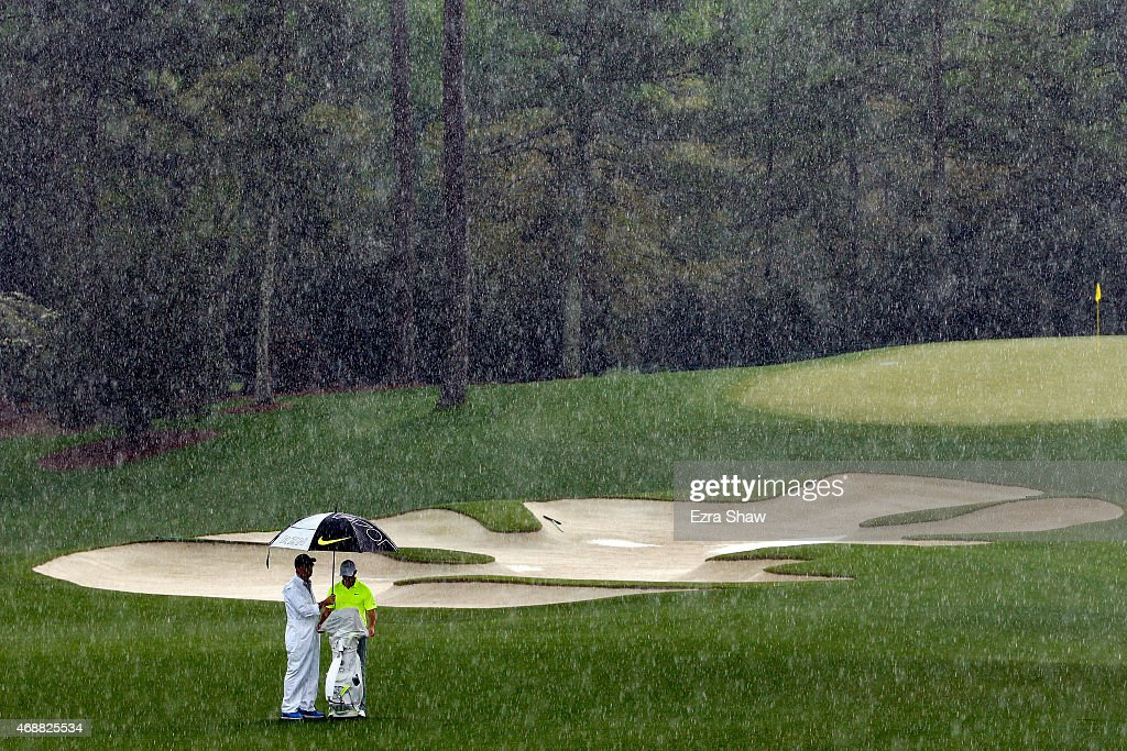 Rory McIlroy of Northern Ireland waits with his caddie J.P. Fitzgerald in the rain during a practice round prior to the start of the 2015 Masters Tournament at Augusta National Golf Club on April 7, 2015 in Augusta, Georgia.