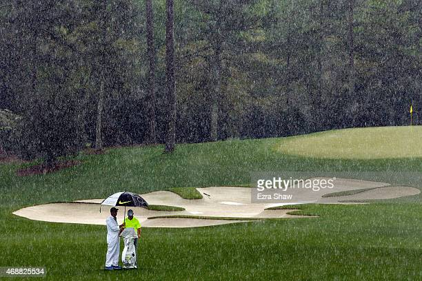 Rory McIlroy of Northern Ireland waits with his caddie JP Fitzgerald in the rain during a practice round prior to the start of the 2015 Masters...