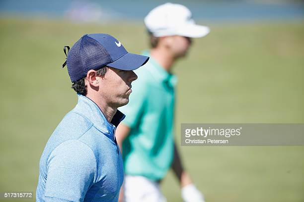 Rory McIlroy of Northern Ireland walks across the 15th green alongside Smylie Kaufman of the United States during the second round of the World Golf...