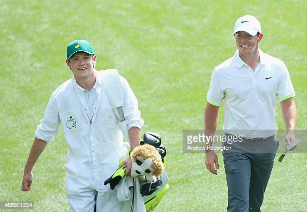 Rory McIlroy of Northern Ireland walks alongside his caddie Niall Horan of the band One Direction during the Par 3 Contest prior to the start of the...