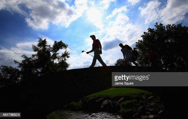 Rory McIlroy of Northern Ireland walks with his caddie JP Fitzgerald across a bridge on the 17th hole during the third round of the BMW Championship...
