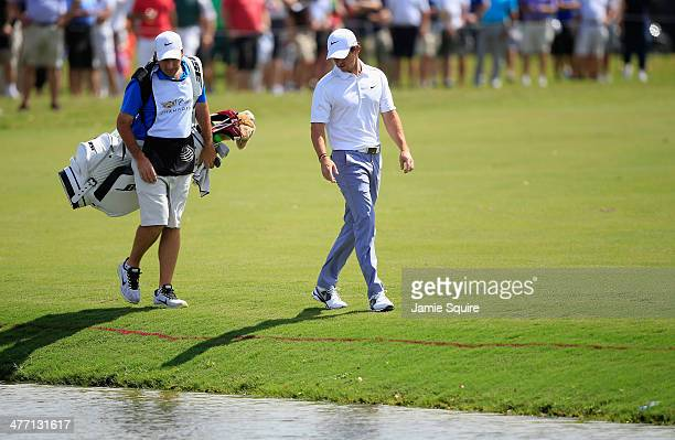 Rory McIlroy of Northern Ireland walks with his caddie JP Fitzgerald after hitting into the water on the first hole during the second round of the...