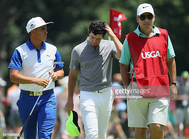 Rory McIlroy of Northern Ireland walks with his caddie JP Fitzgerald and Rickie Fowler of the United States off the ninth green after finishing the...
