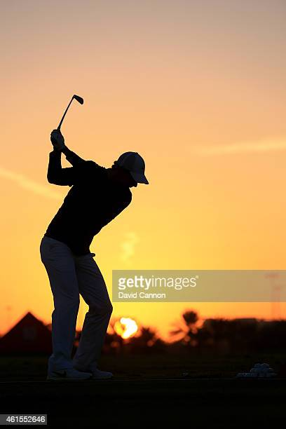 Rory McIlroy of Northern Ireland warms up on the range as the sun rises during the first round of the Abu Dhabi HSBC Golf Championship at Abu Dhabi...