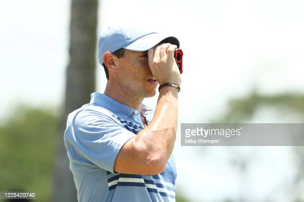 Rory McIlroy of the American Nurses Foundation team uses a rangefinder on the practice range during the TaylorMade Driving Relief Supported By...