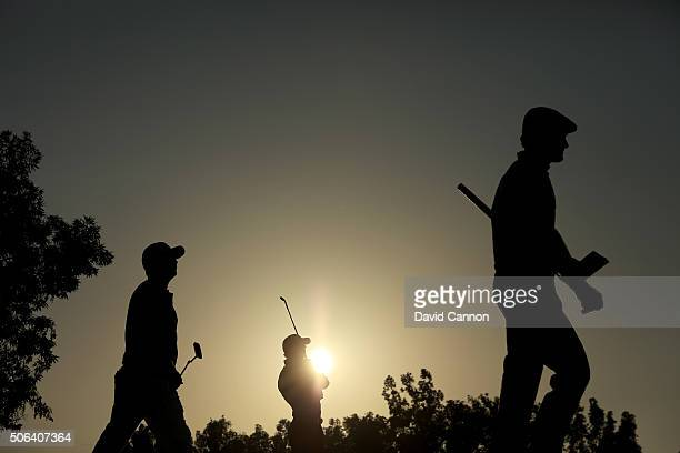 Rory McIlroy plays his tee shot at the par 3 seventh hole as the sun sets as his playing partners Andy Sullivan of England and Brson DeChambeau of...