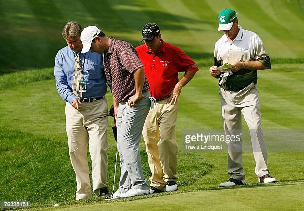 Rory Sabbatini asks for a ruling on the 12th green from rule official Mark Russell as fellow players Rich Beem and Woody Austin look on during the...