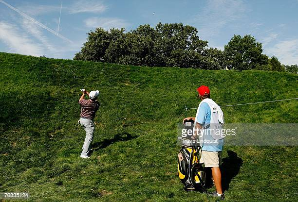 Rory Sabbatini of South Africa hits from the rough on the 14th hole as his caddie Kevin Fasbender watches during the final round of The Barclays the...