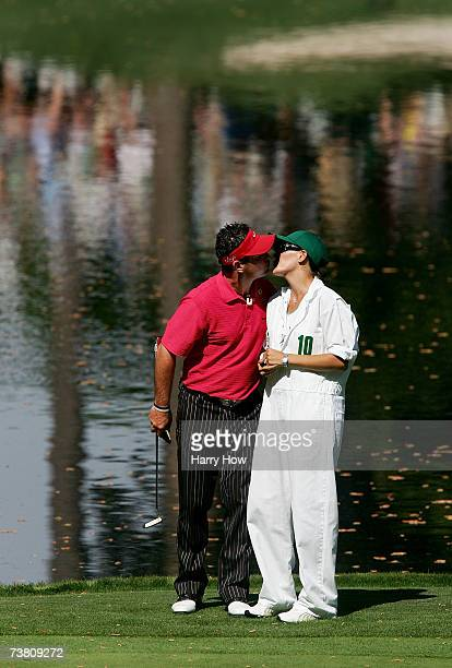 Rory Sabbatini of South Africa kisses his wife Amy on the ninth green during the Par3 contest prior to the start of The Masters at the Augusta...