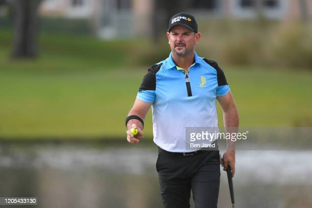 Rory Sabbatini of South Africa waves his ball to fans on the eighth green during the final round of The Honda Classic at PGA National Champion course...
