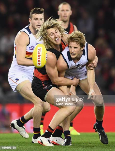 Rory Sloane of the Crows handballs whilst being tackled by Dyson Heppell of the Bombers during the round 21 AFL match between the Essendon Bombers...