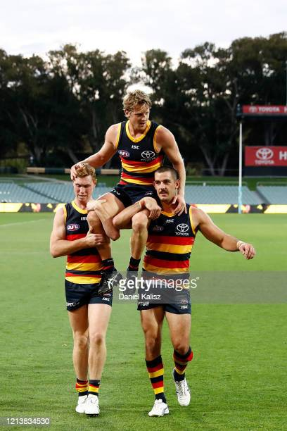 Rory Sloane of the Crows is chaired off by Tom Lynch of the Crows and Taylor Walker of the Crows during the round 1 AFL match between the Adelaide...