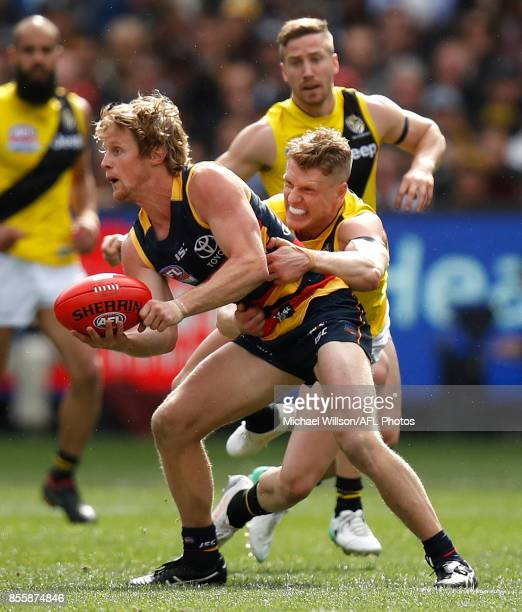 Rory Sloane of the Crows is tackled by Josh Caddy of the Tigers during the 2017 Toyota AFL Grand Final match between the Adelaide Crows and the...