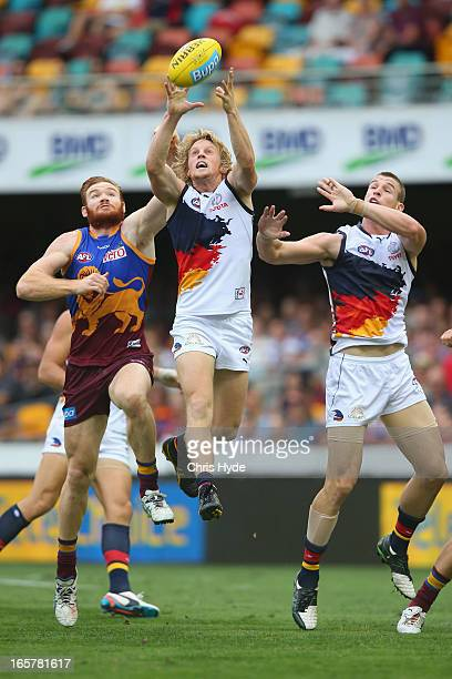 Rory Sloane of the Crows marks the ball over Daniel Merrett of the Lions during the round two AFL match between the Brisbane Lions and the Adelaide...