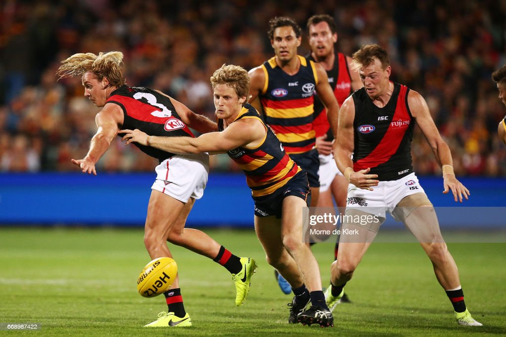 Rory Sloane of the Crows tackles Darcy Parish of the Bombers during the round four AFL match between the Adelaide Crows and the Essendon Bombers at Adelaide Oval on April 15, 2017 in Adelaide, Australia.