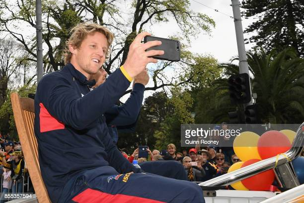 Rory Sloane of the Crows takes photos of the crowd during the 2017 AFL Grand Final Parade on September 29 2017 in Melbourne Australia