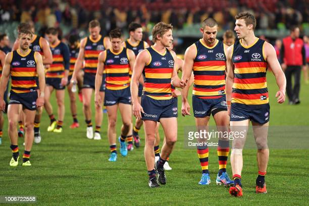Rory Sloane of the Crows Taylor Walker of the Crows and Josh Jenkins of the Crows walk from the ground during the round 19 AFL match between the...