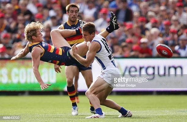 Rory Sloane of the Crows tumbles over Shaun Atley of the Kangaroos during the round one AFL match between the Adelaide Crows and the North Melbourne...