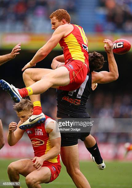 Rory Thompson of the Suns collides into teamate Trent McKenzie and Levi Casboult of the Blues during the round 20 AFL match between the Carlton Blues...