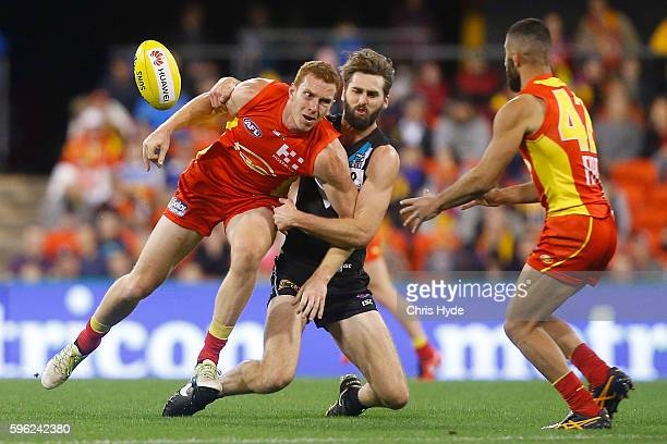Rory Thompson of the Suns is tackled by Justin Westhoff of the Power during the round 23 AFL match between the Gold Coast Suns and the Port Adelaide...