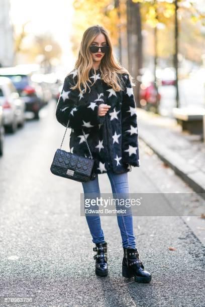 Rosa Crespo fashion blogger wears a Dior black leather bag a Sandro fur coat with white printed stars Zara black leather boots J brand blue denim...