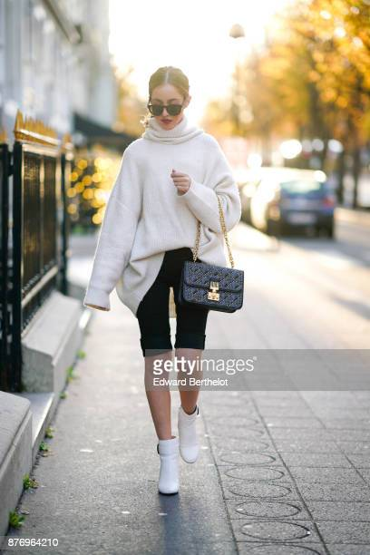 Rosa Crespo fashion blogger wears a Dior studded bag Barney white boots sunglasses an Acne Studios white oversize sleeves sweater and a turtleneck at...
