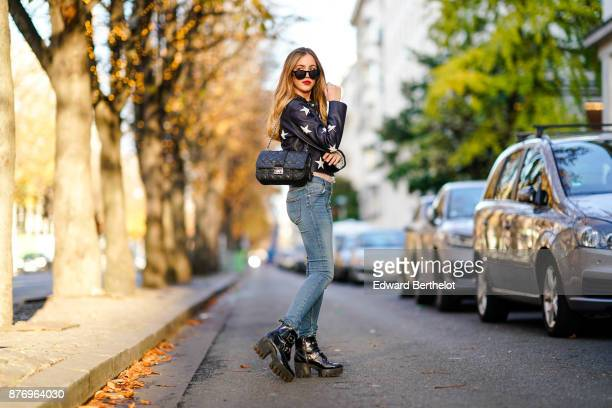 Rosa Crespo fashion blogger wears a Sandro leather jacket with white stars printed sunglasses a Dior bag Jbrand blue jeans black Zara leather boots...