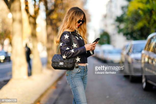 Rosa Crespo fashion blogger wears black sunglasses a Sandro leather jacket with white printed stars a Dior bag blue jeans and is using a smartphone...