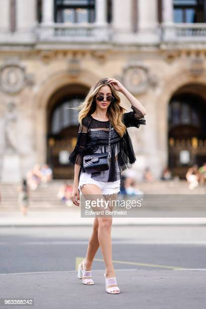 Rosa Crespo, fashion blogger, wears Quay sunglasses, a black lace mesh top, a short, white shoes, a Chanel black leather bag, on May 27, 2018 in...