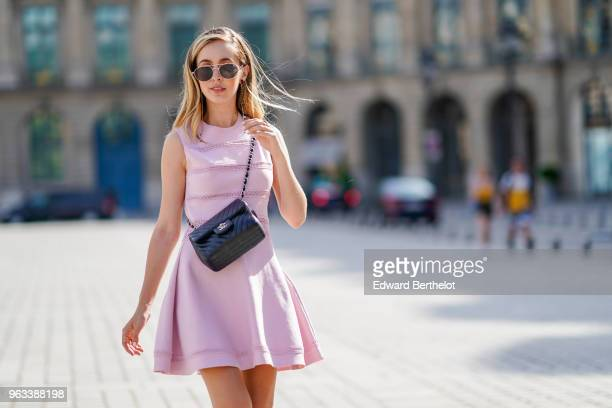 Rosa Crespo fashion blogger wears Quay sunglasses a pink Dior dress with embroidery a Chanel black leather bag on May 27 2018 in Paris France