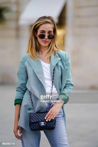 Rosa Crespo fashion blogger wears Quay sunglasses a white tshirt blue denim jeans a Chanel black leather bag a green checked gingham blazer jacket on...