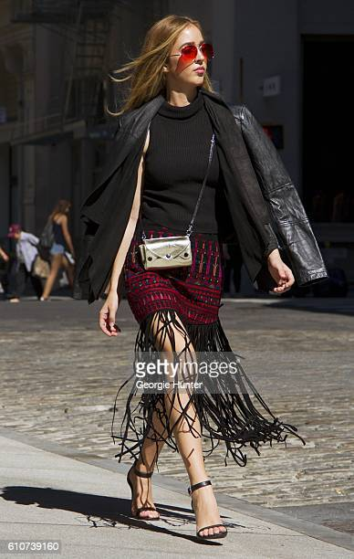 Rosa Crespo wearing black ribbed cotton sleeveless turtleneck top and embroidered suede skirt with long leather fringe from All Things Mochi black...