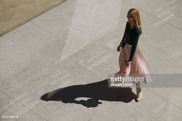 Rosa Crespo wearing silk bubblegum pink pleated midi length high waisted El Corte Ingles lame skirt, green long sleeve Sandro Paris top with ruffle...