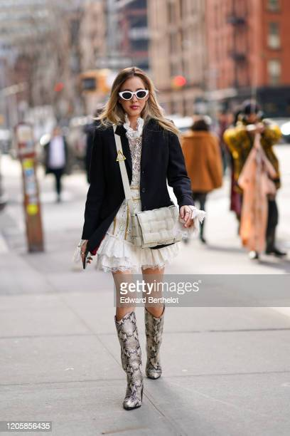 Rosa Crespo wears white sunglasses, a black jacket, a white quilted bag from Bottega Veneta, a white lace mesh ruffled dress, gray snake pattern...