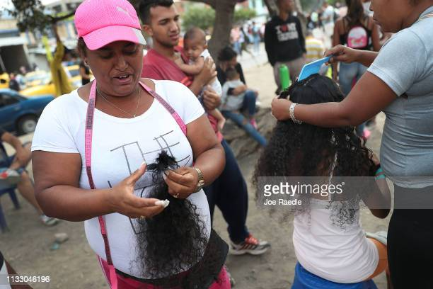 Rosa Mendez holds the hair of a woman that she purchased and cut from her head to make hair extensions after the woman crossed the border from...
