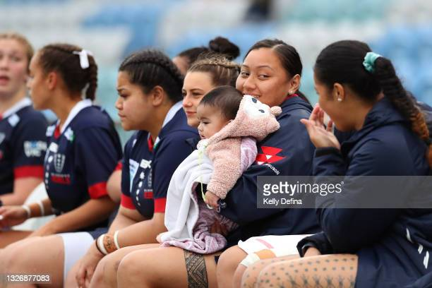 Rosalia Leumuava of the Rebels looks on while holding an assistant coaches baby during the Super W match between the Melbourne Rebels and the ACT...