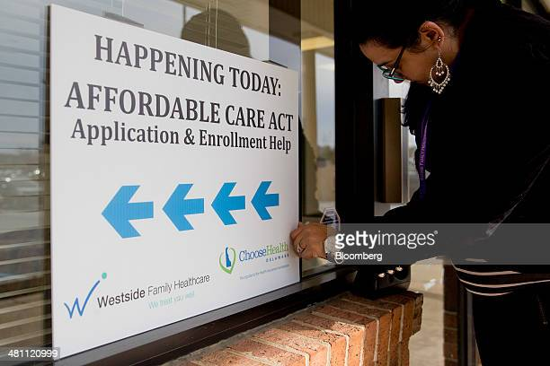 Rosalia Ramirez tapes an Affordable Care Act application and enrollment help sign at a Westside Family Healthcare center in Bear, Delaware, U.S., on...