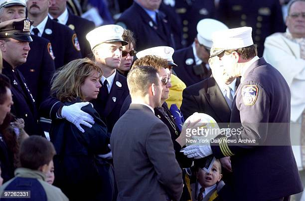 Rosalie Downey is presented with firefighter helmet as family members look on during memorial service for her husband Deputy Chief Raymond Downey at...