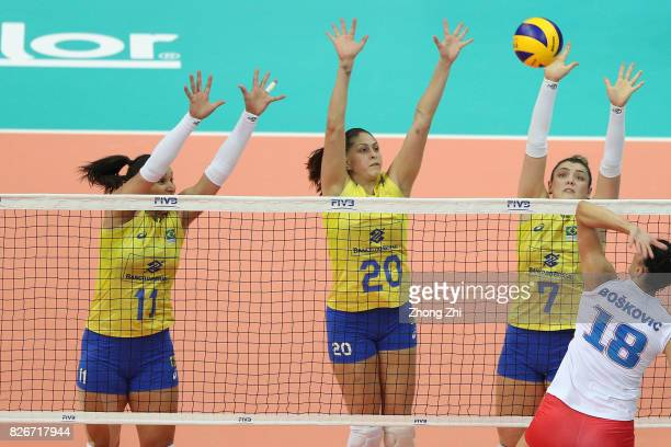 Rosamaria Montibeller #11 Tandara Caixeta and Ana Beatriz Correa of Brazil in action during the semi final match between Brazil and Serbia during...