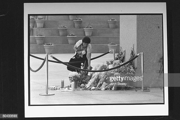 Rosamond Bagan placing flowers at memorial at the base of the office tower at 101 CA street where Gian Luigi Ferri a disgruntled client toting two...