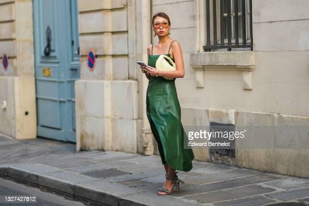 Rosana Lai wears gold pendant earrings, sunglasses, gold rings, a gold bracelet, a green shiny leather sleeveless cut-out midi split dress, a pale...