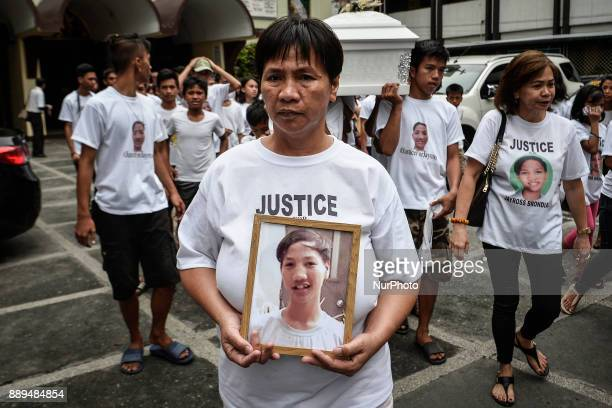 Rosanna Brondial holds a picture of her 13yearold son Jayross Brondial who was killed by an unidentified gunman during his funeral in Pasay Metro...