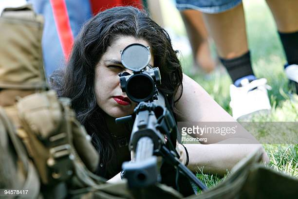 Rosanne Bezerra looks through the scope of a Barrett 50caliber sniper rifle during a helicopter raid demonstration with Marines from the Marine...