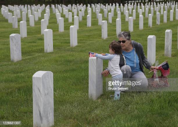 Rosanne D'Angelo of Commack and granddaughter Morgan visit her father's grave at Calverton National Cemetery on May 23 2020 in Wading River New York...