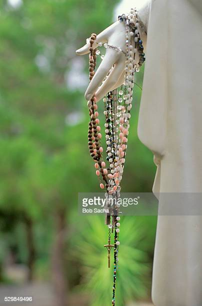 rosaries draped over the hand of a statue - rosary beads stock pictures, royalty-free photos & images