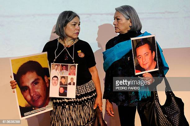 Rosario Villanueva and Yolanda Moran hold pictures of their missing sons Oscar German Herrera and Dan Jeremeel Fernandez who disappeared in 2009 and...