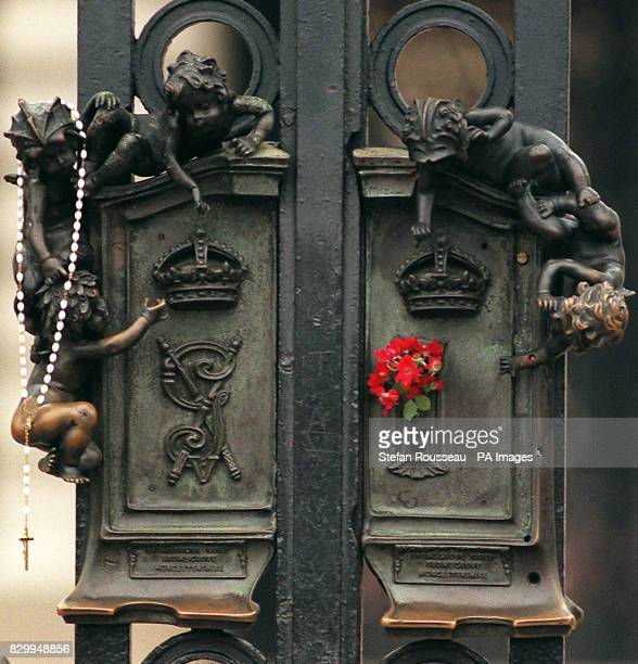 A rosary and a simple bouquet of flowers placed on the Royal Crest on one of the gates of Buckingham Palace this morning