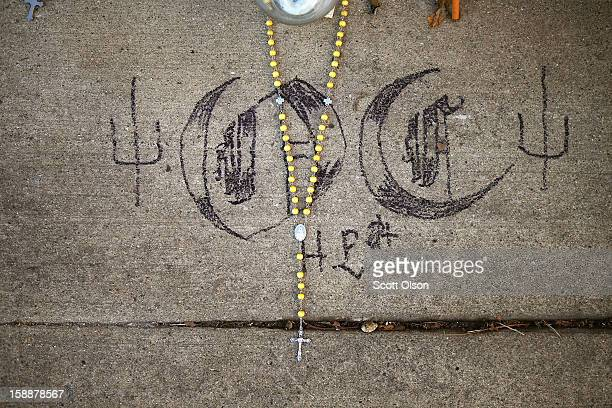 A rosary and gang symbols are part of a memorial created in an alley near the spot where 20yearold Octavius Dontrell Lamb was shot yesterday and...