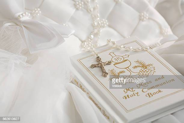 Rosary beads, cross and book on first communion dress