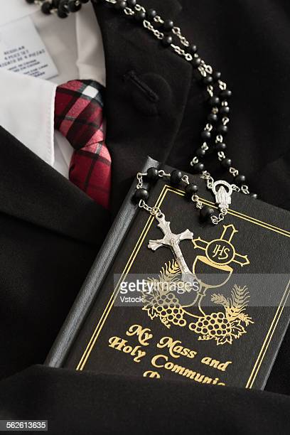 Rosary beads with silver cross, holy book, formal clothes